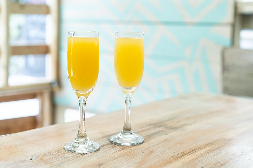 Two glasses of mimosas on top of a wooden table