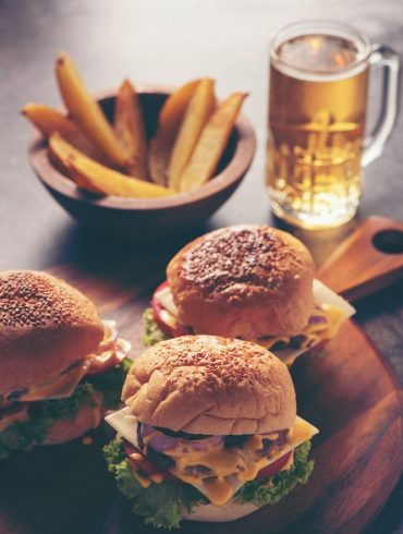 Three burgers sit on top of a wooden serving platter alongside French fry wedges and a beer